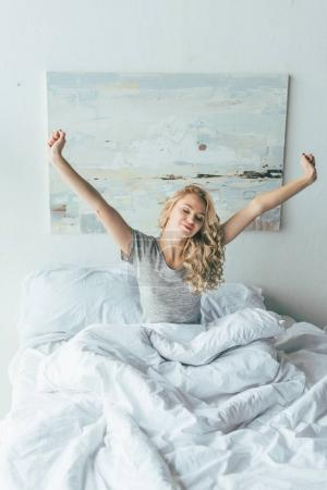 Photo for Beautiful smiling young woman waking up and stretching in bed - Royalty Free Image