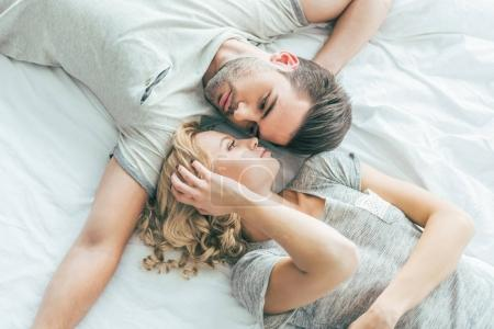 Photo for Beautiful young couple in love looking at each other while lying together on bed - Royalty Free Image