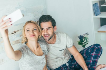couple using smartphone in bed