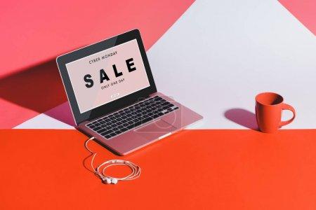 Photo pour Tasse de café, des écouteurs et des ordinateur portable avec un écran blanc sur blanc et rouge - image libre de droit