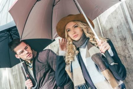 Stylish young couple with umbrellas