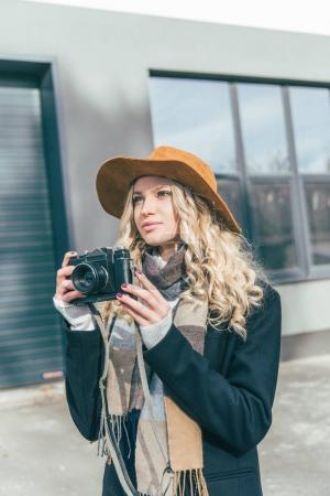 Photo pour Belle jeune femme au chapeau, appareil photo et à la recherche de loin sur la rue - image libre de droit
