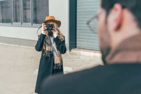 woman with camera photographing boyfriend