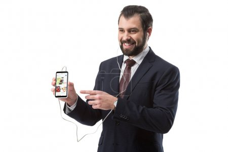 Photo for Cheerful bearded businessman listening music with earphones and pointing at smartphone with ebay website, isolated on white - Royalty Free Image