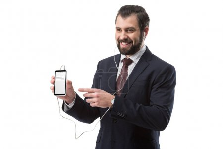 Photo for Cheerful bearded businessman listening music with earphones and pointing at smartphone with website, isolated on white - Royalty Free Image