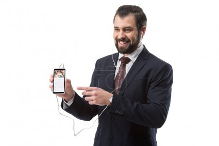 Photo pour Homme d'affaires barbu gai écoute la musique avec des écouteurs et pointant sur smartphone avec site foursquare, isolé sur blanc - image libre de droit