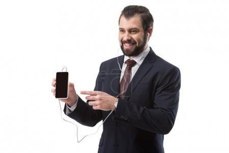 Photo for Cheerful bearded businessman listening music with earphones and pointing at smartphone, isolated on white - Royalty Free Image