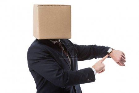 Photo pour Homme d'affaires avec une boîte en carton sur la tête pointant sur montre, isolé sur blanc - image libre de droit