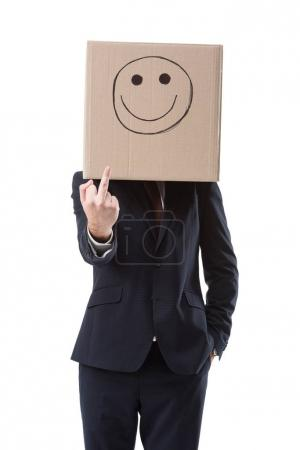Photo for Businessman with box with smile sign on head showing middle finger, isolated on white - Royalty Free Image