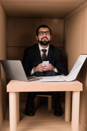 Photo pour Homme d'affaires utilisant un smartphone et travaillant avec un ordinateur portable en carton dans la boîte - image libre de droit