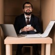 Businessman using smartphone and working with cardboard laptop in box