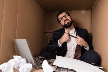 Photo pour Homme d'affaires enlever la cravate tout en travaillant avec un ordinateur portable en carton dans la boîte - image libre de droit