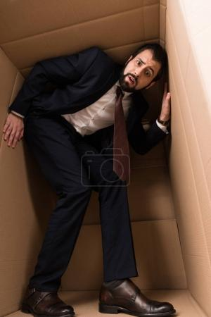 businessman with claustrophobia inside a box
