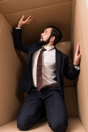 Photo for Businessman with claustrophobia kneeling in cardboard box - Royalty Free Image