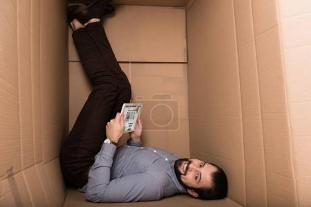 Photo pour Homme souriant, à l'aide de tablette numérique avec site de nourriture de bbc dans boîte en carton - image libre de droit