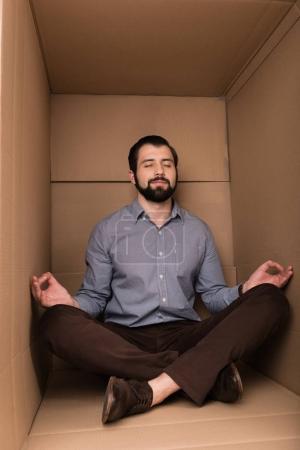 man meditating in cardboard box