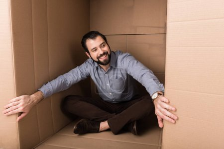 Photo for Cheerful man sitting in cardboard box, introvert concept - Royalty Free Image