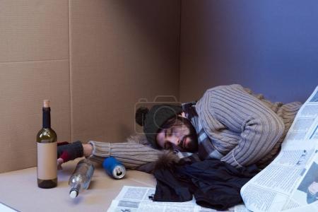 homeless man sleeping in box