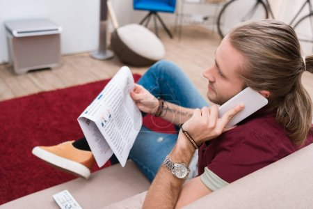 handsome man reading newspaper and talking on smartphone at home
