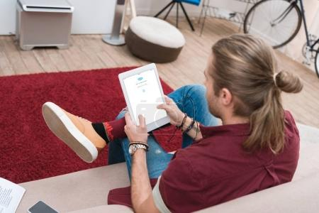 man sitting on sofa while using digital tablet with skype appliance