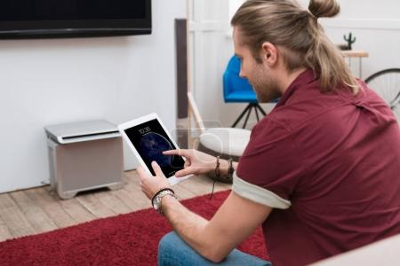 Photo for Man sitting on sofa while using ipad tablet - Royalty Free Image
