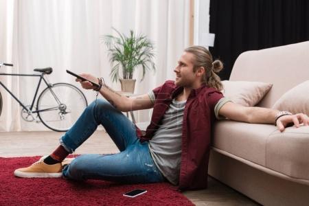 Photo pour Bel homme avec télécommande regarder la tv à la maison - image libre de droit
