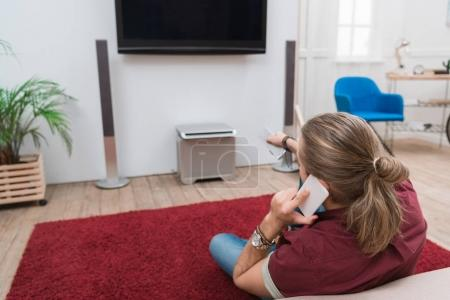 rear view of man talking on smartphone and watching tv at home