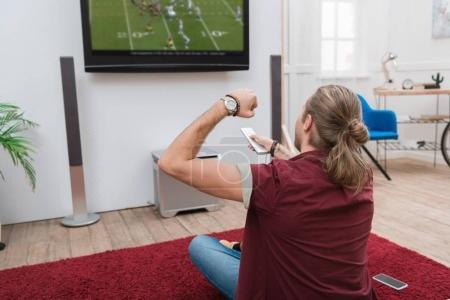 back view of man watching football match and cheering at home