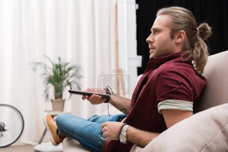 handsome concentrated man with remote control watching tv at home