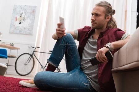 handsome man with remote control and smartphone at home