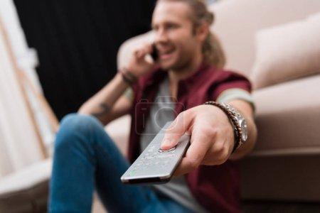 Photo pour Mise au point sélective de l'homme avec télécommande regarder la tv - image libre de droit