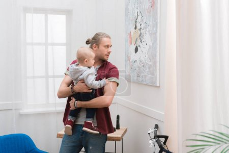 dad holding his little son on hands at home