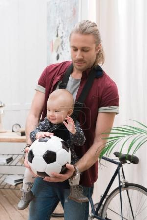 father with son in baby sling holding a football ball