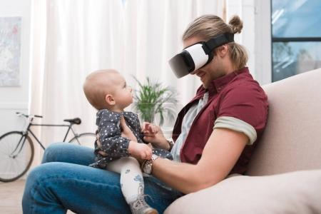 smiling father sitting with his little daughter and using Virtual reality headset