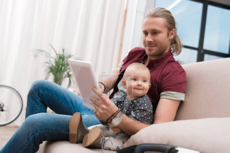 father using digital tablet while sitting with his little daughter