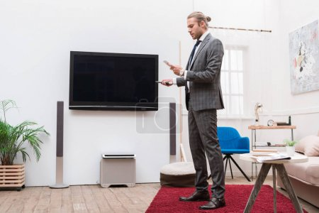 Businessman looking at smartphone and holding remote controller