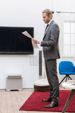 Businessman standing in a living room and reading newspaper
