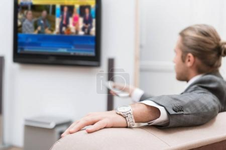 Businessman sitting at home and watching TV