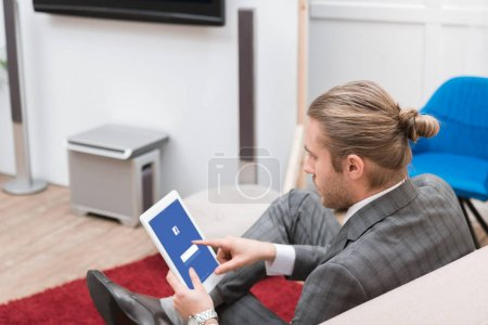 Photo for Businessman using digital tablet with facebook website at home - Royalty Free Image