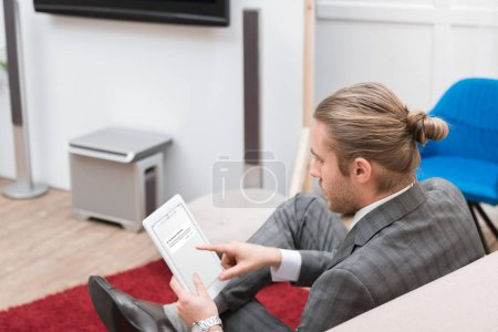 businessman using digital tablet with vk website at home