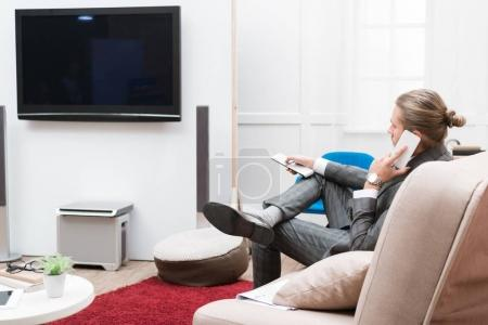 businessman talk on smartphone while watching television at home