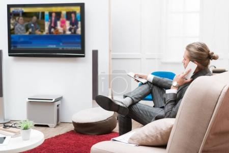 Businessman talking by smartphone and changing TV channels at home