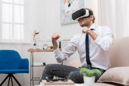 businessman fighting and using Virtual reality headset while sitting on sofa at home