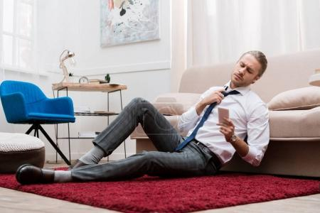Businessman sitting on a carpet, loosening tie and looking at smartphone