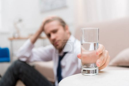 Businessman sitting on a floor at home and taking glass of water