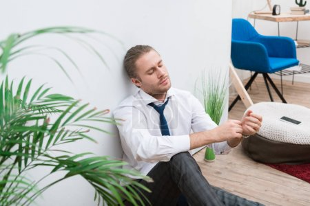 Tired businessman sitting on a floor at home