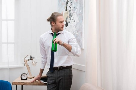Handsome man standing and holding bottle of beer in the living room