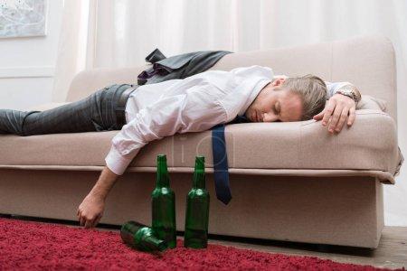 Photo pour Homme ivre dort sur un canapé dans le salon - image libre de droit