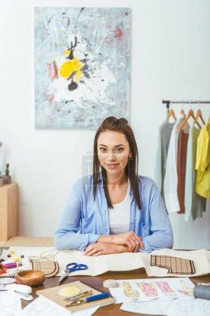 attractive seamstress sitting at working table and looking at camera