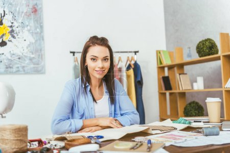 beautiful seamstress sitting at working table and looking at camera